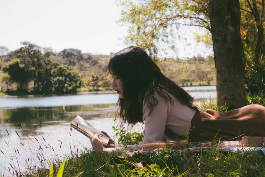 A girl reading a book on the grass