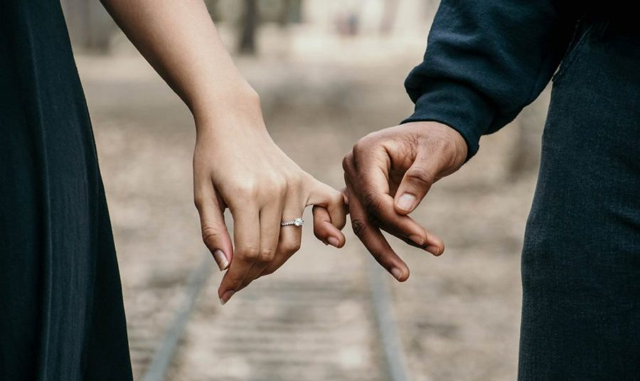 A couple holding each other's little finger
