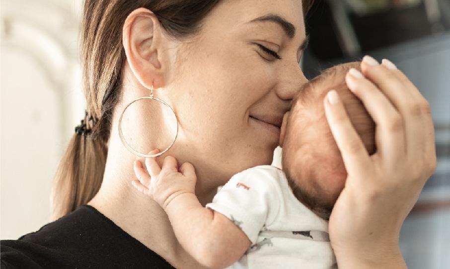 Loving mother holding her newborn baby tight